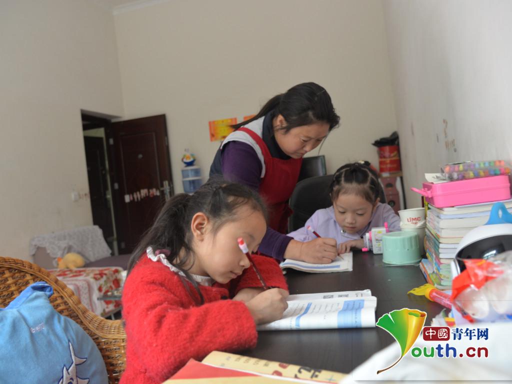 马海英为小女儿,小女儿的同学辅导家庭作业.通江县委宣传部供图